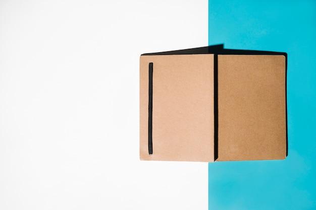 Geschlossenes notizbuch mit brauner bucht auf weißem und blauem hintergrund Kostenlose Fotos