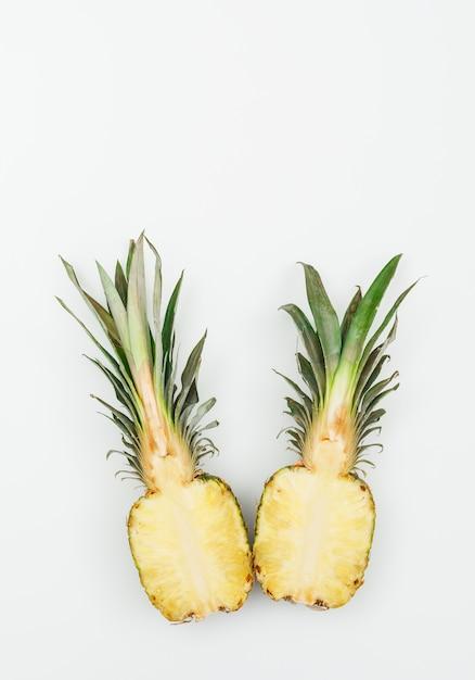 Geschmackvolle ananas halbiert auf einem weiß. draufsicht. Kostenlose Fotos