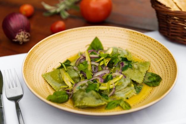 Geschmackvolle grüne ravioliteigwaren mit zwiebel und basilikum verlässt in der keramischen platte Kostenlose Fotos