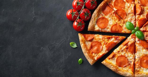 Geschmackvolle pepperonipizza auf schwarzem konkretem hintergrund Premium Fotos