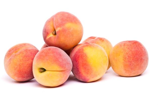 Geschmackvolle pfirsiche auf weiß Premium Fotos