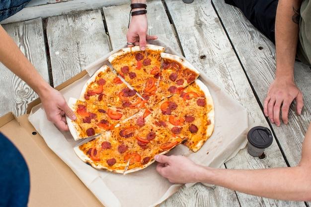 Geschmackvolle pizza im kasten auf holzoberfläche Kostenlose Fotos