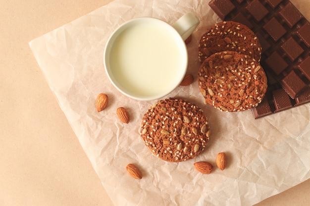 Geschmackvolle selbst gemachte hafermehlplätzchen auf einer platte mit nüssen, schale milch auf einem hellen hintergrund, draufsicht. Premium Fotos