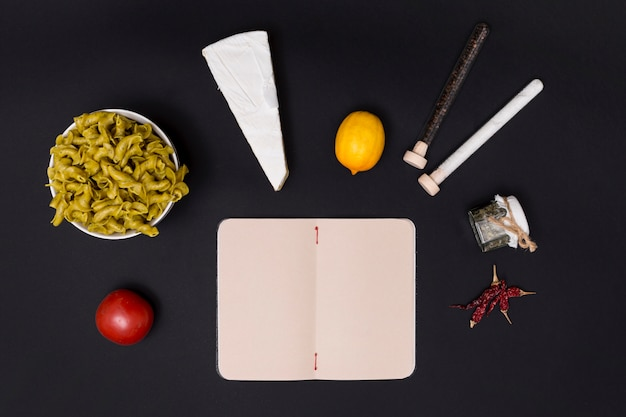 Geschmackvoller bestandteil für teigwaren mit offenem leerem tagebuch auf schwarzer oberfläche Kostenlose Fotos