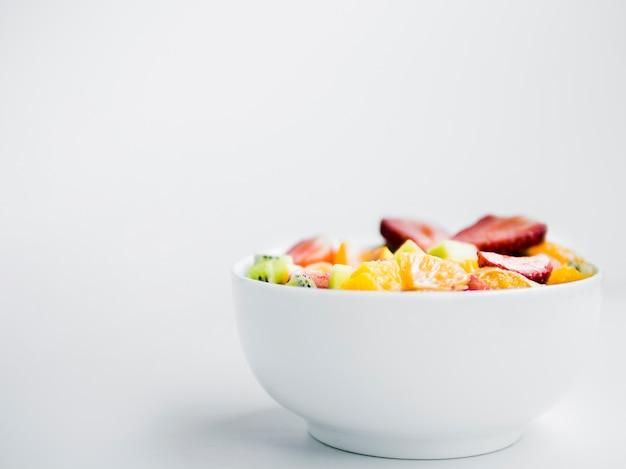 Geschmackvoller frischer obstsalat in der schüssel auf weißem hintergrund Kostenlose Fotos