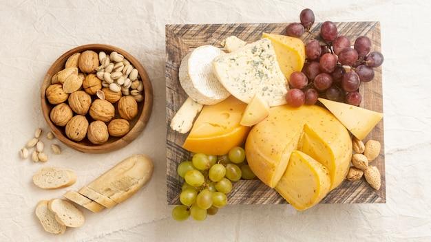 Geschmackvoller käse der draufsicht mit trauben und nüssen Kostenlose Fotos