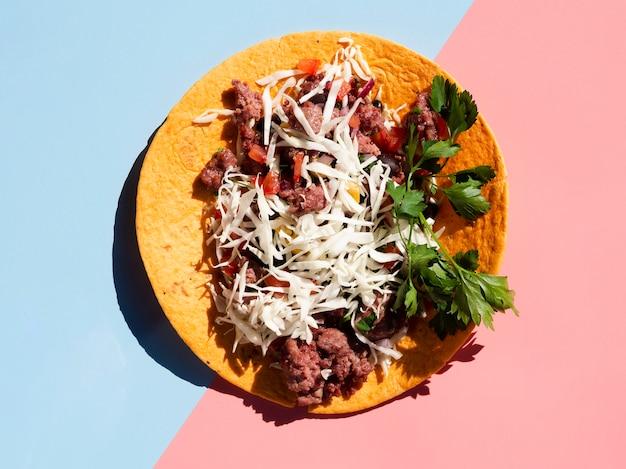 Geschmackvoller mexikanischer taco mit fleisch und veggies auf kontrastiertem blauem und rosa hintergrund Kostenlose Fotos