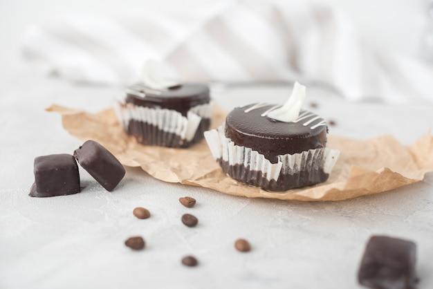 Geschmackvoller schokoladenkleiner kuchen und kaffeebohnen auf pergamentpapier Kostenlose Fotos