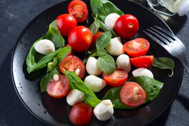 Geschmackvoller und schöner caprese-salat auf der schwarzen keramischen platte, abschluss oben Premium Fotos