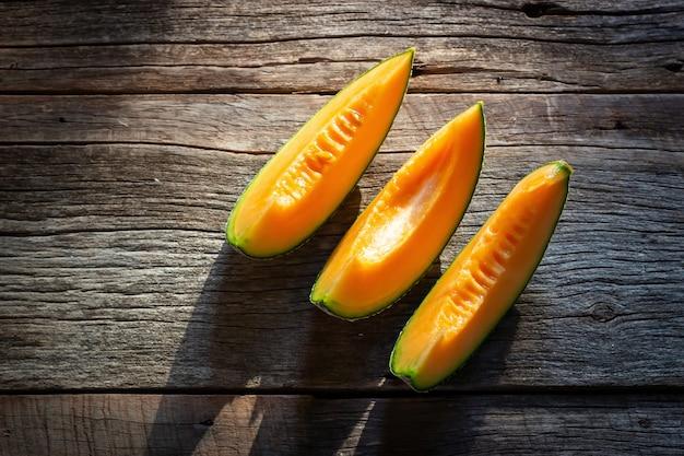 Geschnittene frische süße melone auf hölzernem brett. orange textur draufsicht Premium Fotos