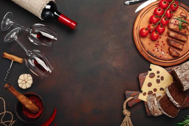 Geschnittene gegrillte schweinefleischsteaks auf einem schneidebrett mit kirschtomaten, käse, brot, knoblauch und rosmarin Premium Fotos