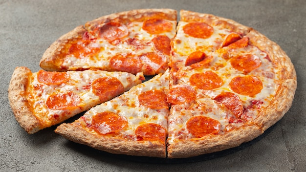 Geschnittene heiße pepperonipizza auf einem braunen hintergrund. Premium Fotos