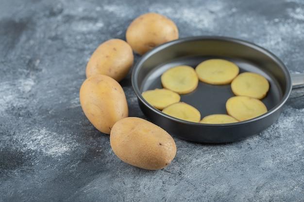 Geschnittene kartoffeln innerhalb der pfanne auf grauem hintergrund. hochwertiges foto Kostenlose Fotos