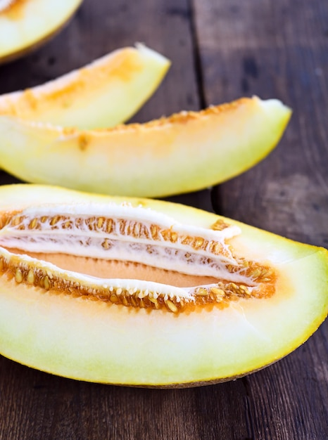 Geschnittene melone auf einem braunen holztisch Premium Fotos