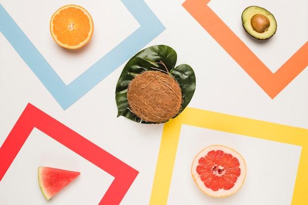 Geschnittene orange pampelmusenwassermelonenavocado und -kokosnuss am monstera-blatt Kostenlose Fotos