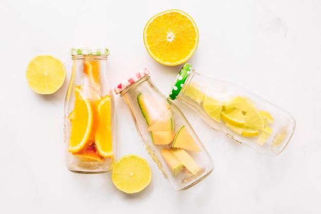 Geschnittene orangen- und glasflaschen mit geschnittener zitrusfrucht Kostenlose Fotos