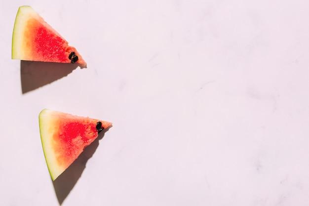 Geschnittene reife wassermelone auf rosa oberfläche Kostenlose Fotos