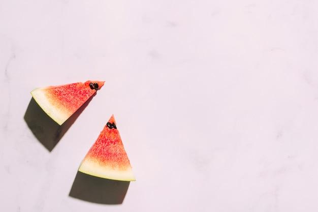 Geschnittene rote wassermelone auf rosa oberfläche Kostenlose Fotos