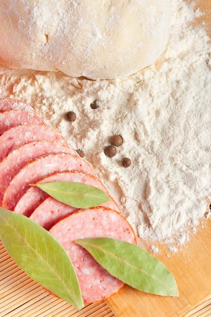 Geschnittene salami, lorbeerblätter und teig Premium Fotos