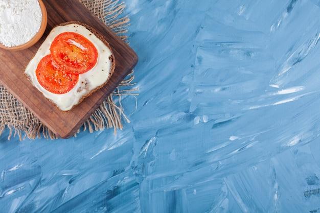 Geschnittene tomaten auf käsebrot und eine schüssel mehl auf schneidebrett auf leinenserviette auf blau. Kostenlose Fotos