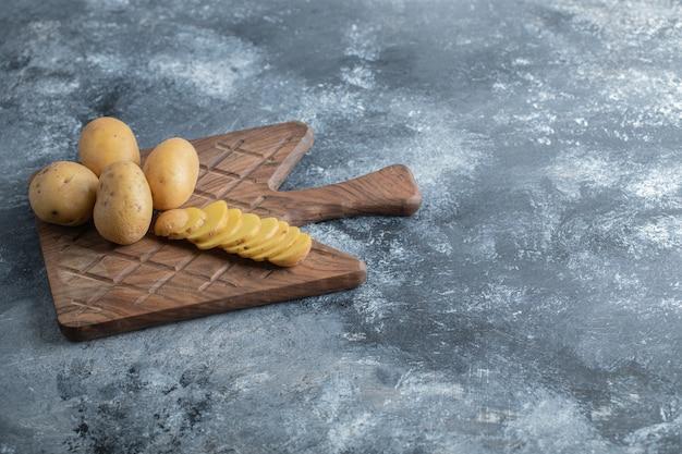 Geschnittene und ganze kartoffeln auf dem holzschneidebrett. hochwertiges foto Kostenlose Fotos