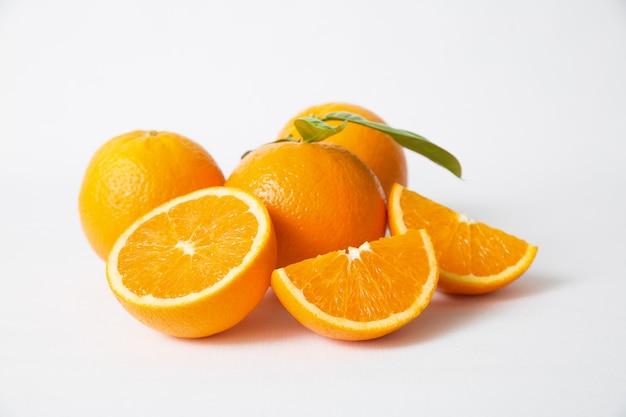 Geschnittene und ganze orangenfrüchte mit grünen blättern Kostenlose Fotos