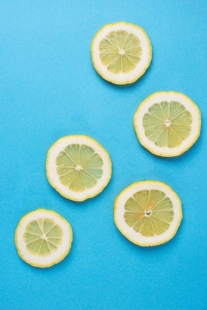 Geschnittene zitrone auf blauem hintergrund Premium Fotos
