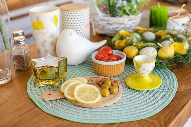 Geschnittene zitronen, oliven, mandeln auf einem holzbrett, ostereier auf dem großen familientisch Kostenlose Fotos