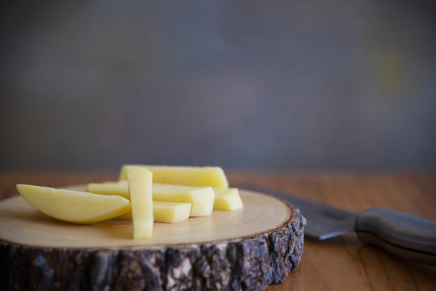 Geschnittener kartoffelstock bereit zur herstellung von pommes-frites - traditionelles lebensmittelzubereitungskonzept Kostenlose Fotos