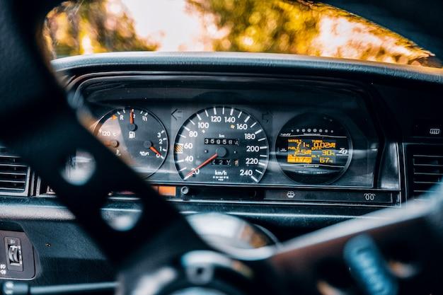 Geschwindigkeitsmesser und kraftstoffverbrauchsmesser eines autos hinter dem richtungssteuerrad Kostenlose Fotos