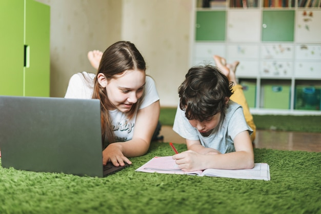 Geschwister bruder schwester attraktives mädchen teenager und tween junge machen hausaufgaben lernen fremdsprache schreiben in schülerbuch mit geöffnetem laptop im raum nach hause diktatur bildung Premium Fotos