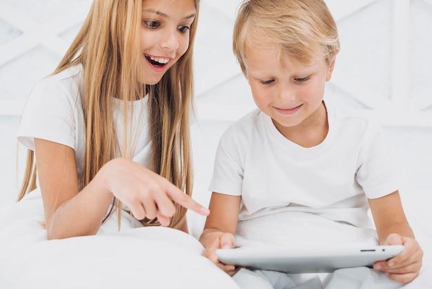 Geschwister, die etwas lustig auf einer tablette aufpassen Kostenlose Fotos