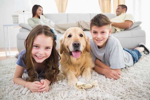 Geschwister, die mit hund während eltern entspannen auf sofa liegen Premium Fotos