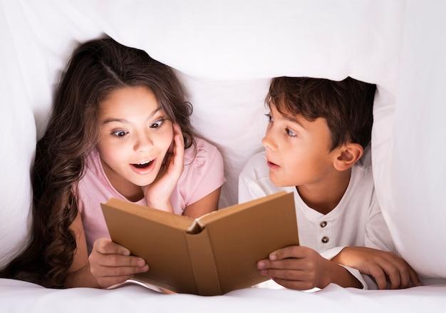 Geschwister schlafen und lesen geschichten Kostenlose Fotos