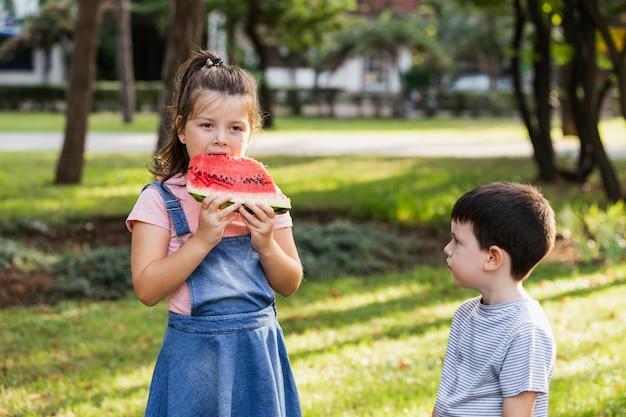 Geschwisterzeit in der natur und mädchen, die wassermelone essen Kostenlose Fotos