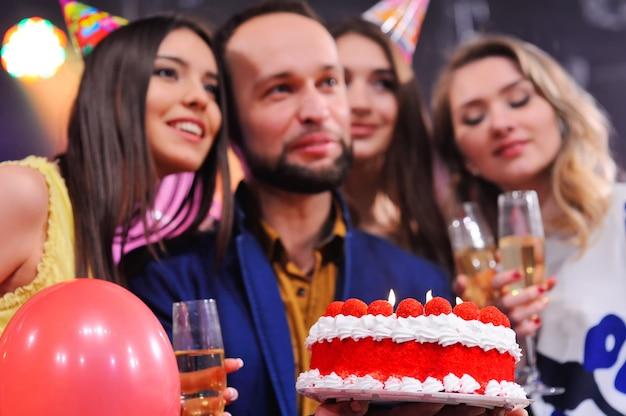Gesellschaft fröhlicher freunde in festlichen hüten, um das ereignis zu feiern Premium Fotos