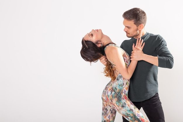 Gesellschaftstanz, bachata, salsa, kizomba, zouk, tangokonzept - mann umarmt frau, während er über weiße wand mit kopienraum tanzt Premium Fotos