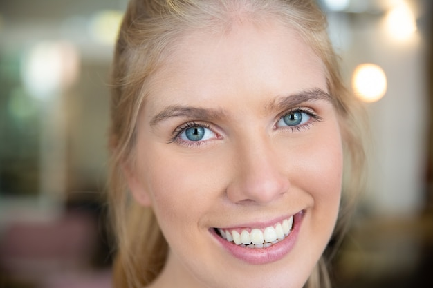 Gesicht der glücklichen schönen jungen blonden frau mit blauen augen und weißen zähnen Kostenlose Fotos
