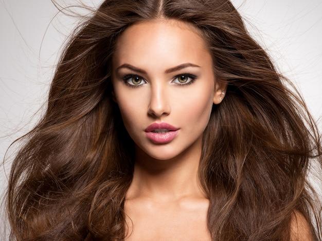 Gesicht der schönen frau mit dem langen braunen haar, das im studio aufwirft Kostenlose Fotos