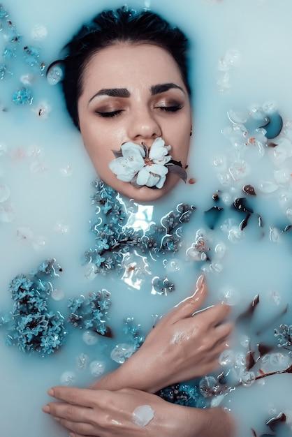 Gesicht eines jungen mädchens mit einer blume im mund und einem blumenstrauß von fliedern entspannend und im bad mit blauer milch genießend Premium Fotos