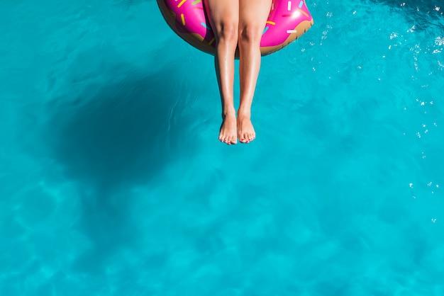 Gesichtslose frau, die auf aufblasbaren ring schwimmt Kostenlose Fotos