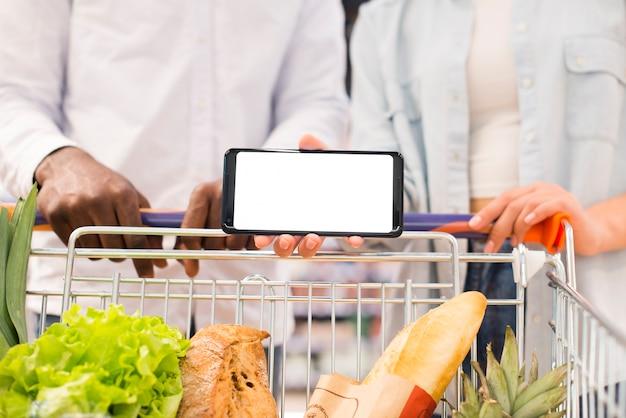 Gesichtslose paare mit dem warenkorb, der smartphone am supermarkt hält Kostenlose Fotos