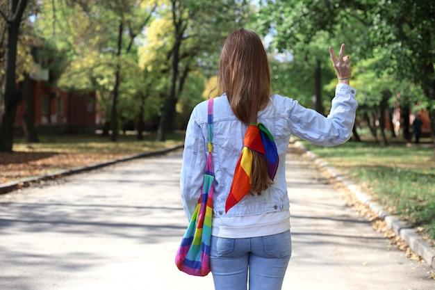 Gesichtsloses mädchen mit regenbogenschal, tasche und armband macht siegeszeichen mit ihrer hand. stolzkonzept Premium Fotos