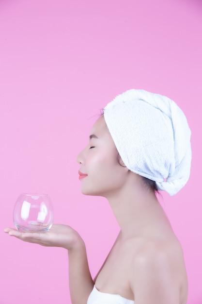 Gesichtsmaskenauflagen-rosahintergrund der jungen frau. Kostenlose Fotos