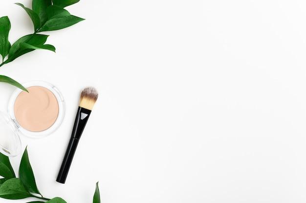 Gesichtspuder in runder hülle und pinsel draufsicht mit grünem blatt Premium Fotos