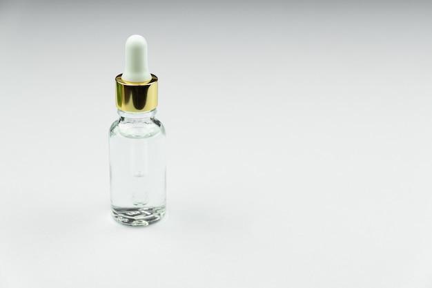 Gesichtsserum in einer glasverpackung, flasche auf einem weißen neutralen hintergrund. Premium Fotos
