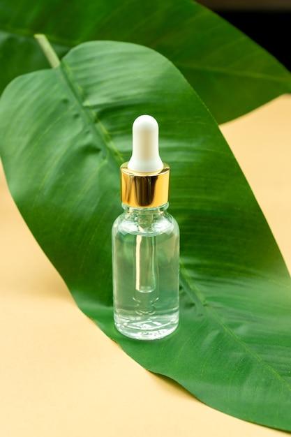 Gesichtsserum in einer transparenten glasflasche auf einem grünen blatt und beige hintergrund. Premium Fotos