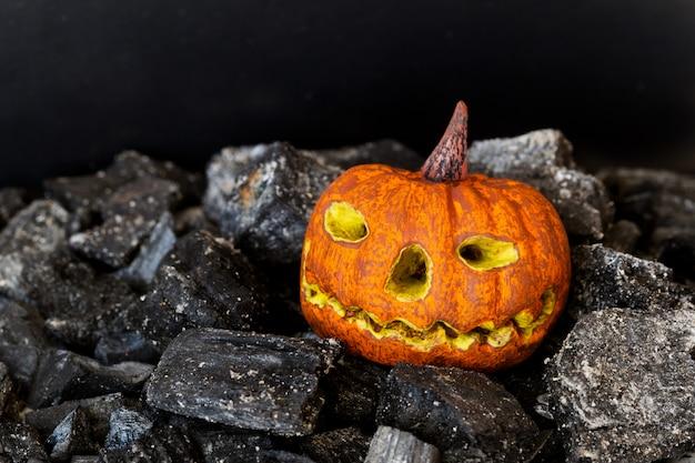 Gespenstisches modell des halloween-kürbises auf dunkler holzkohle. nahaufnahme, vorgewählter fokus Premium Fotos