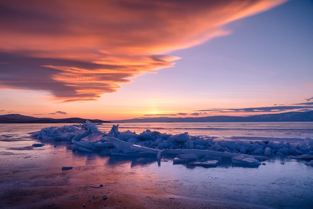 Gestalten sie bild des natürlichen brechenden eises über gefrorenem wasser bei drastischem sonnenuntergang auf dem baikalsee, sibirien, russland landschaftlich. Premium Fotos
