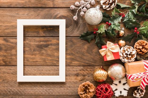 Gestalten sie in der nähe von geschenkboxen, grünen zweigen, schmuckstücken und weihnachtskugeln Kostenlose Fotos